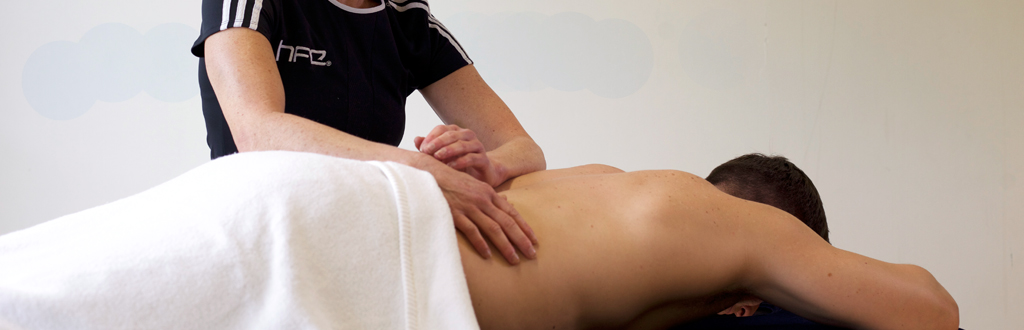 Qualified sports massage therapist working with a client