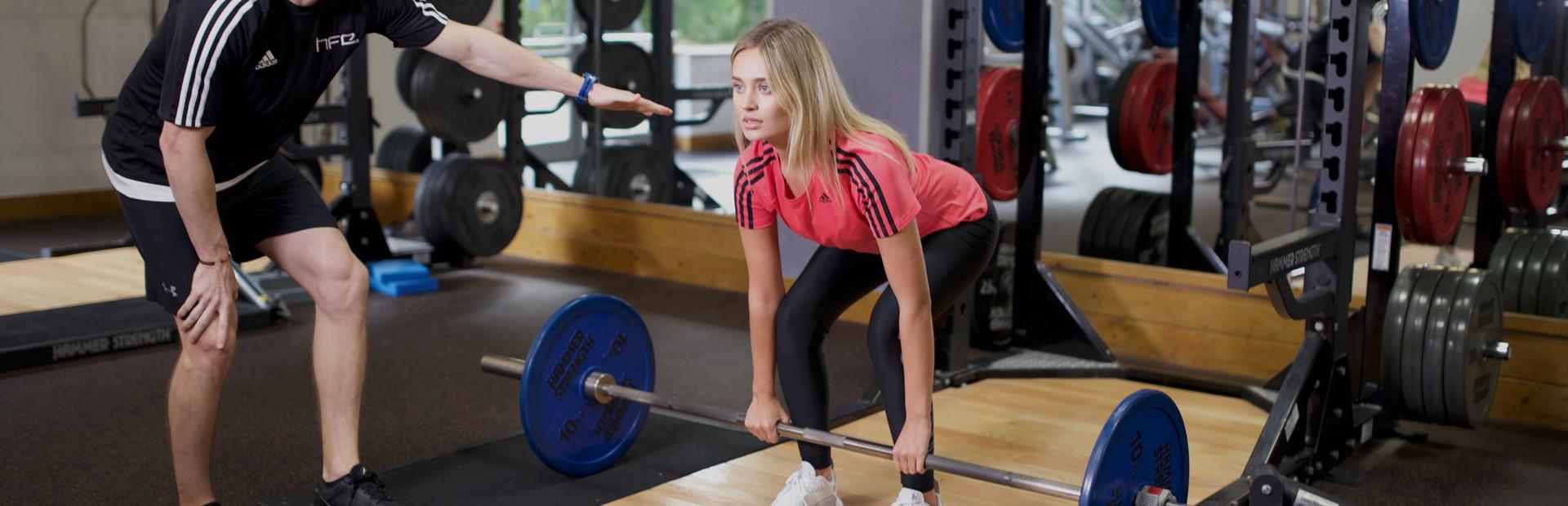 Personal training tutor coaching a deadlift