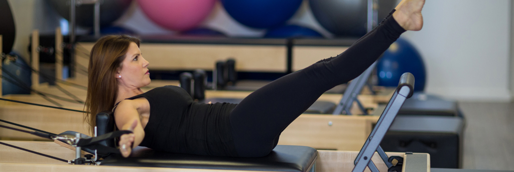 A woman taking part in a reformer Pilates class
