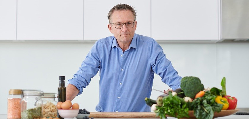 Dr Mosley posing in his kitchen